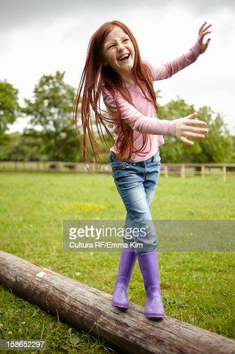 Girl balancing on wooden log