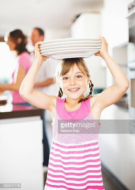 Girl (8-9) balancing plates on her head , smiling