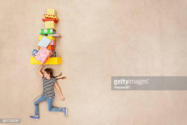 Girl balancing stack of presents
