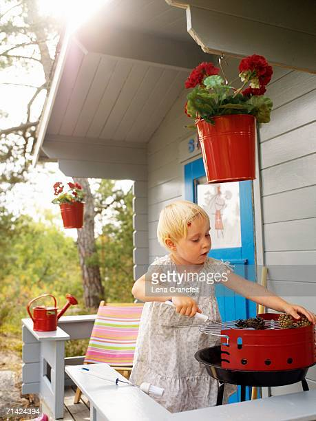 Girl barbequing on the porch of a playhouse.