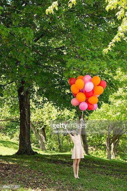 Girl being lift by bouquet of balloons in spring nature.