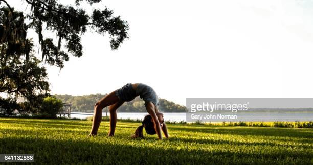 Girl bending over backwards in backbend or crab position, outdoors