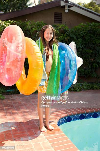 girl beside pool holding inflatable tubes