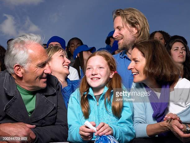 Girl (8-10) between grandparents in stadium crowd, close-up