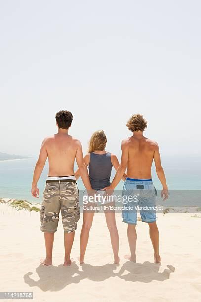 A girl between two boys facing the sea