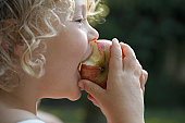 'Girl (3-5) biting into apple, profile, close-up'