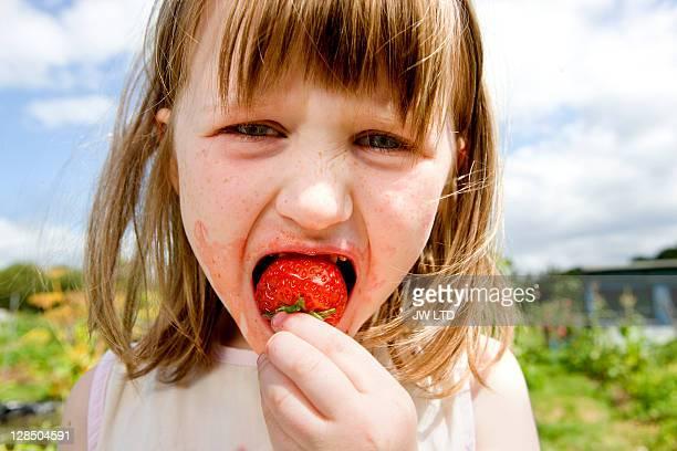 Girl biting strawberry, close up
