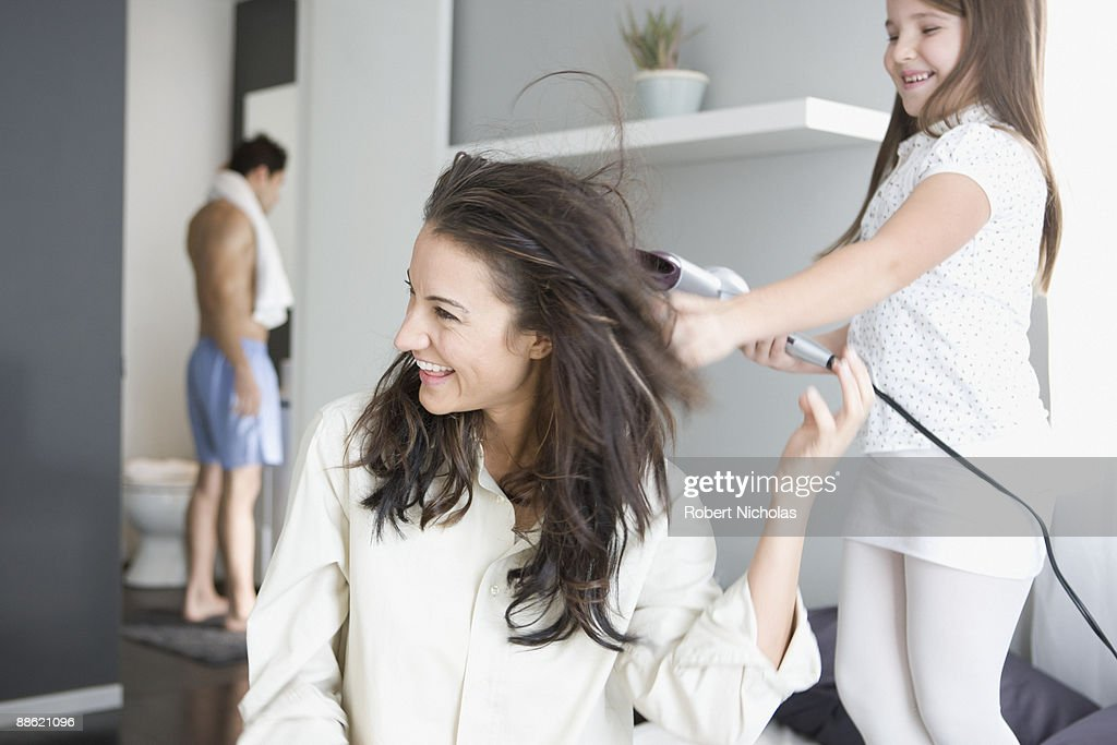 Girl blow drying mothers hair