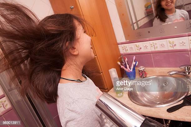 Girl blowdrying her hair in bathroom. Spain