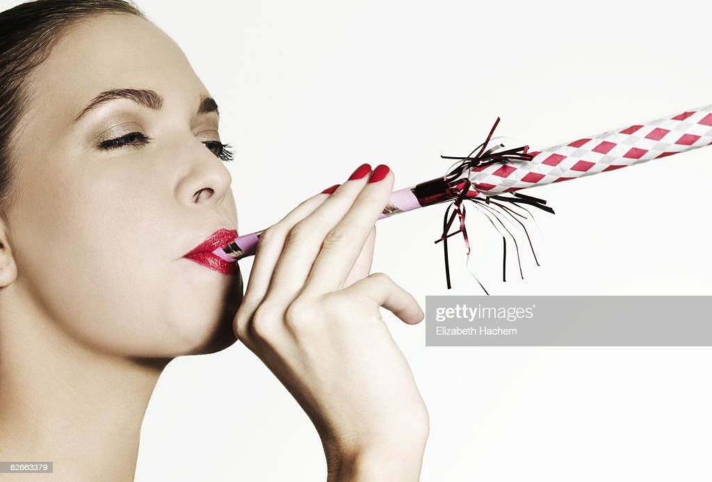 Girl blowing a party favour : Stock Photo
