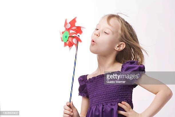 Girl blowing at pinwheel or windmill
