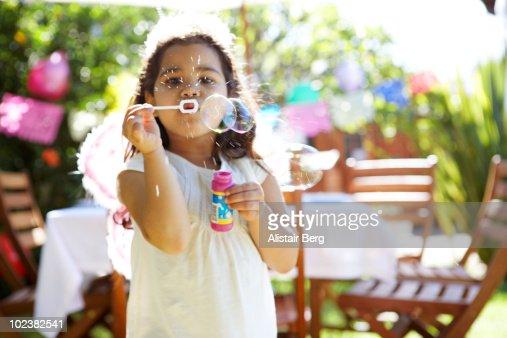 Girl blowing bubbles in garden