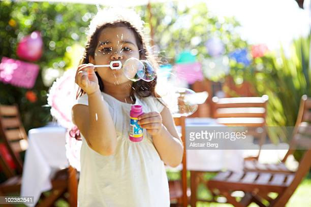 Girl blowing bubbles in garden