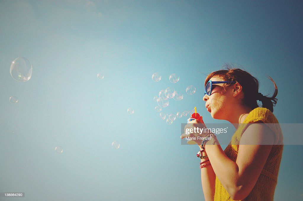 Girl blowing bubbles into blue sky : Stock Photo