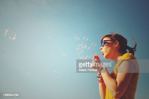 Girl blowing bubbles into blue sky