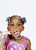 Girl (2-4) blowing bubbles through bubble wand, portrait