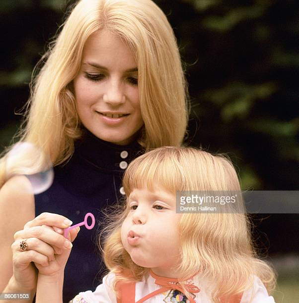 Girl blowing bubbles while mother smiles