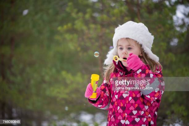 Girl Blowing Bubbles While Standing Against Trees