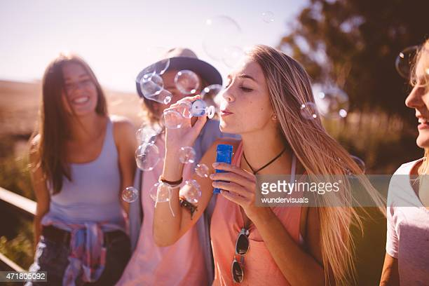 Girl blowing bubbles with a group of friends