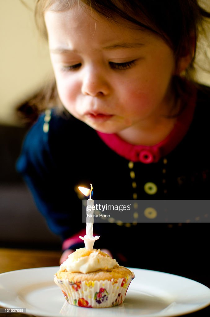 Girl blowing candle : Stock Photo