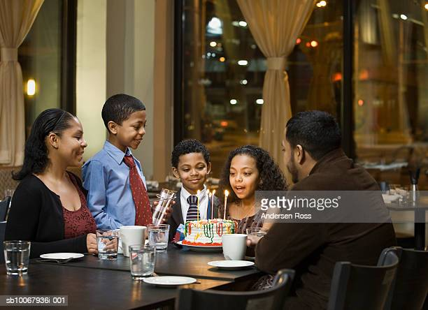 Girl (10-11) blowing candles on birthday cake in restaurant