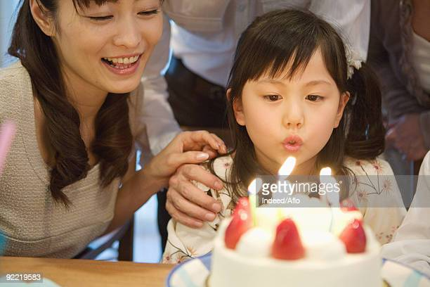 Girl blowing candles with her mother