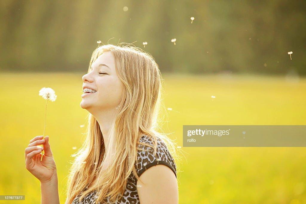 Girl blowing dandelion seed