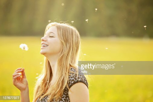 Girl blowing dandelion seed