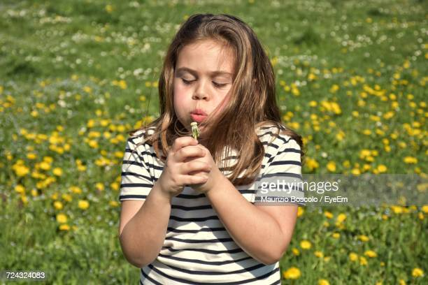 Girl Blowing Dandelion While Standing On Field