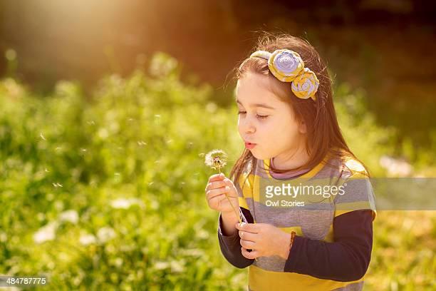 Girl blowing dandellion