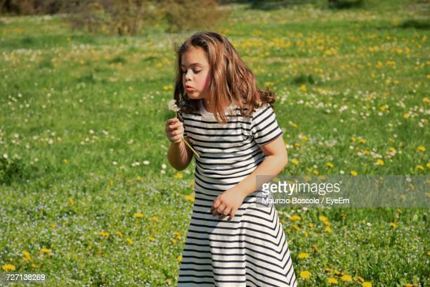 Girl Blowing Flower While Standing On Field