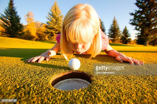 Girl Blowing Golf Ball Into Cup