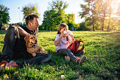 Girl blowing nose and sitting on grass with father and small yellow dog