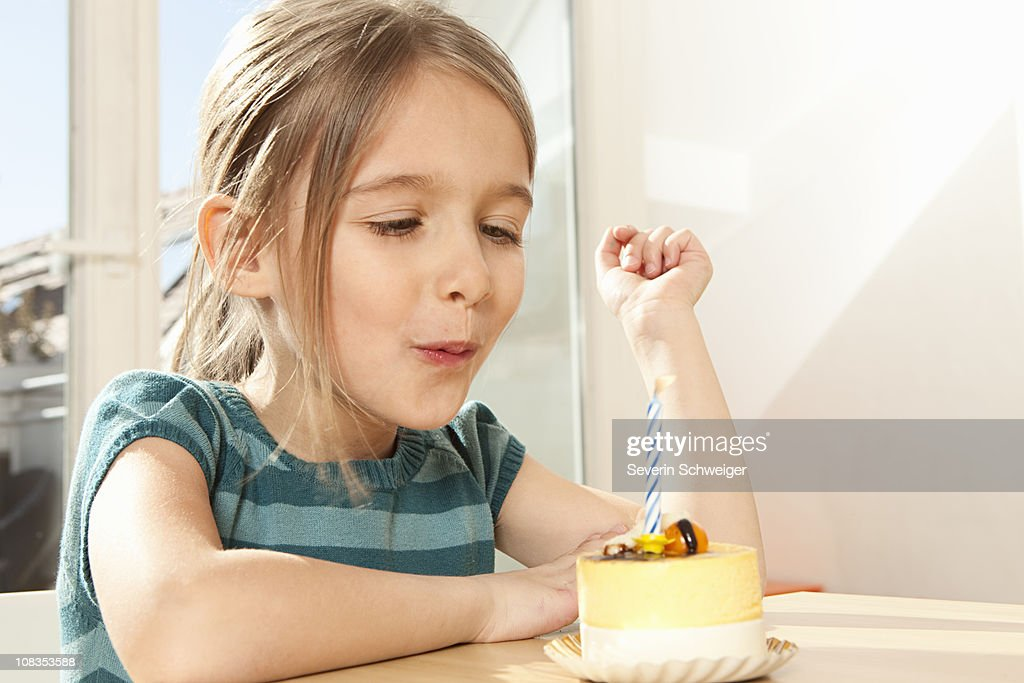 Girl blowing out candle on birthday cake : Stock Photo