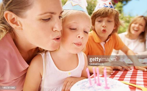 Fille soufflant les bougies sur le gâteau d'anniversaire
