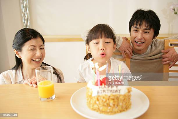 Girl blowing out candles on a birthday cake with their parents beside her