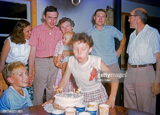 Girl (13-15) blowing out candles on birthday cake as family looks on