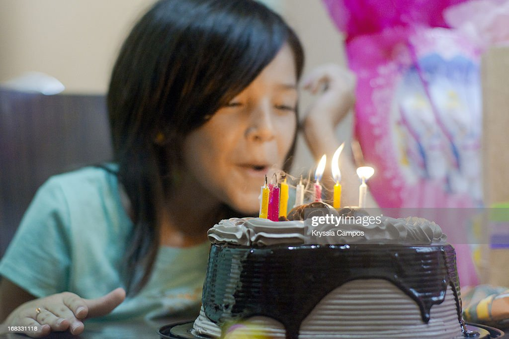 Girl blowing out candles on birthday cake : Stock Photo