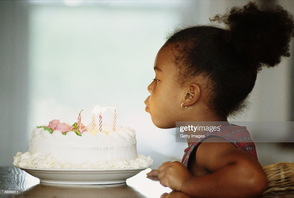 Girl (4-6) blowing out candles on birthday cake : Stock Photo