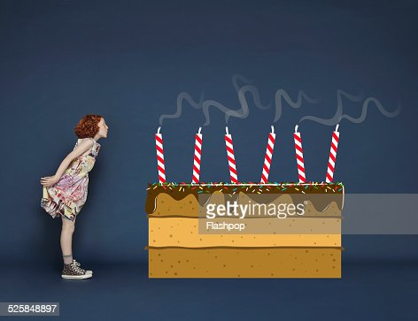Girl blowing out candles on cartoon birthday cake