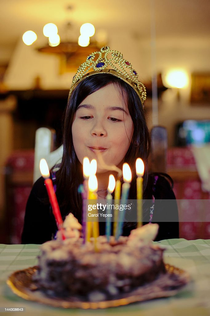 Girl blowing out candles : Stock Photo