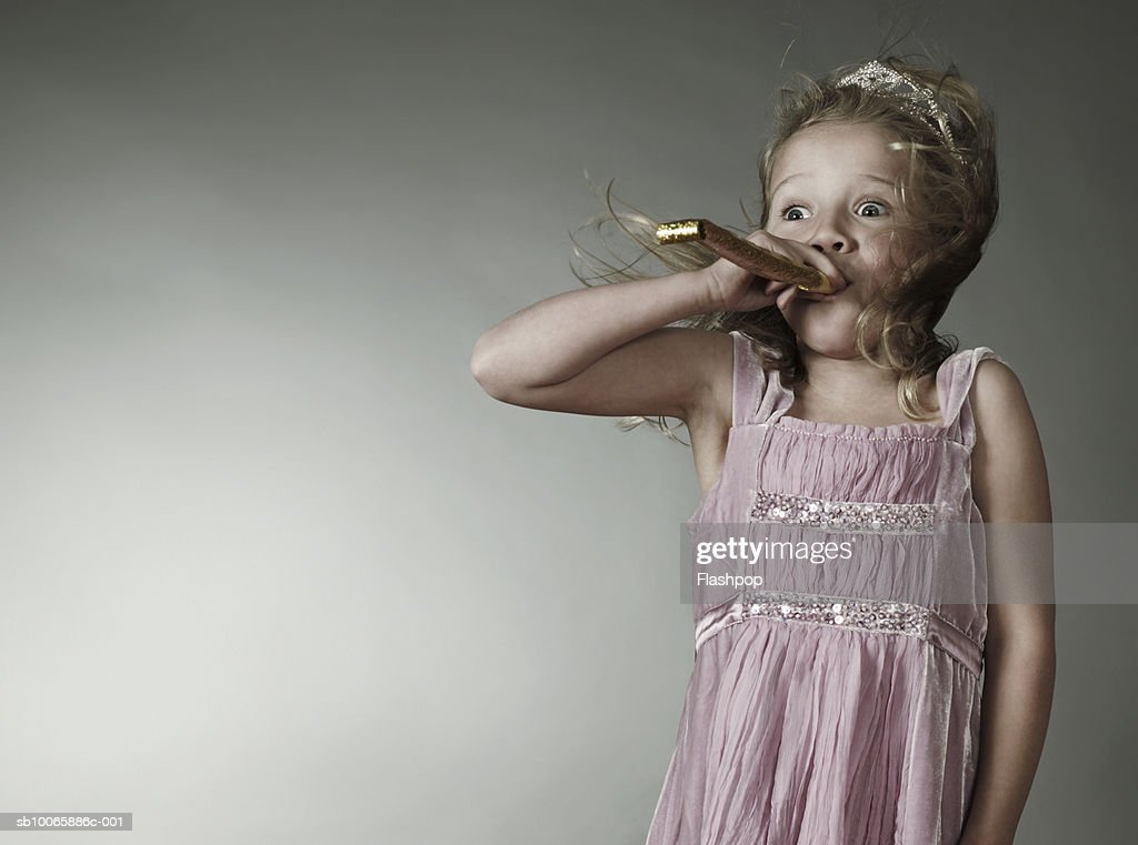 Girl (6-7) blowing party blower : Stock Photo