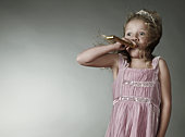 Girl (6-7) blowing party blower