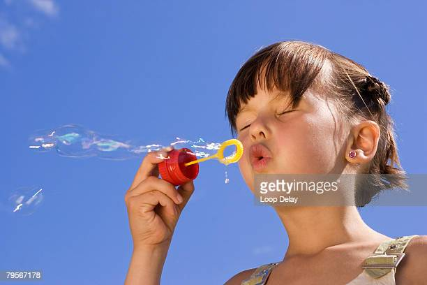 'Girl (7-9) blowing soap bubbles, eyes closed'