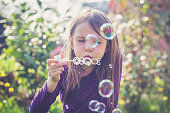 Girl blowing soap bubbles in a garden