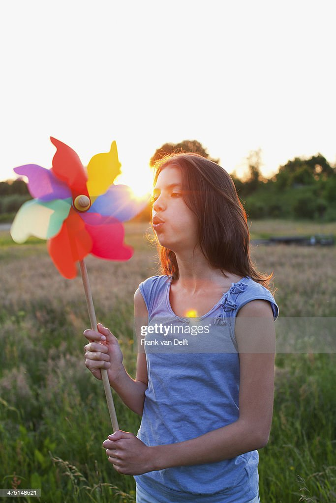 Girl blowing toy windmill : Stock Photo