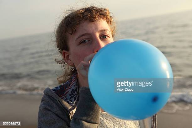 Girl blowing up a balloon in the beach