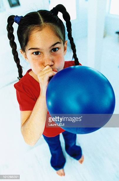 Girl blowing up a balloon
