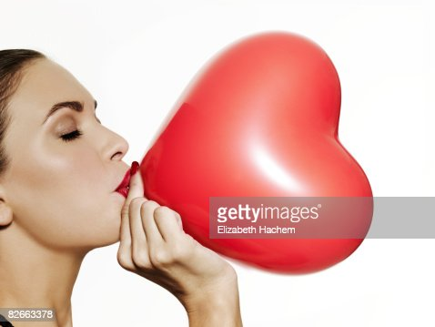 Girl blowing up a red heart shaped balloon : Stock Photo