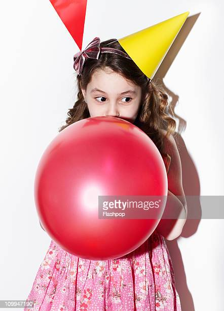 Girl blowing up balloon at party